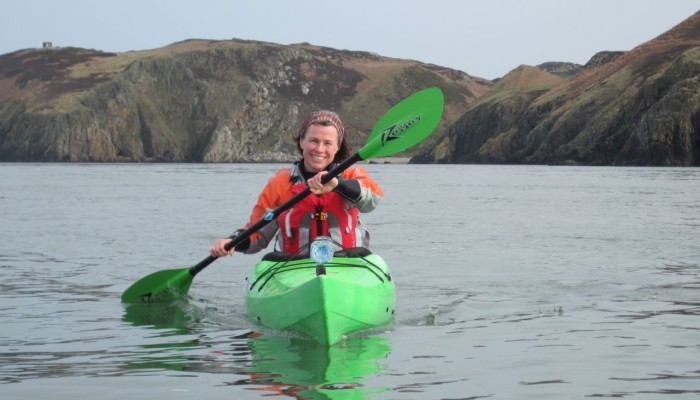 Photo of a woman in a sea kayak in Cemaes Bay, Anglesey