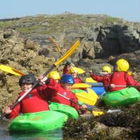 Photo of some kids kayaking in between some rocks