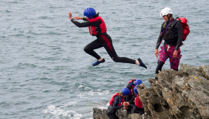 Photo of someone jumping into the sea while coasteering watched by an instructor