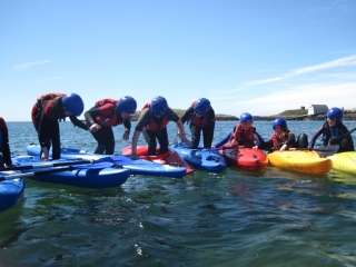 Kayak group playing games in Rhoscolyn