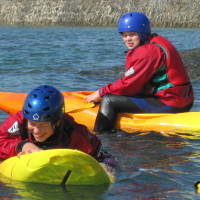 young people getting wet whilst kayaking