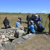 Photo of a group of walkers gathered round discussing a ruin